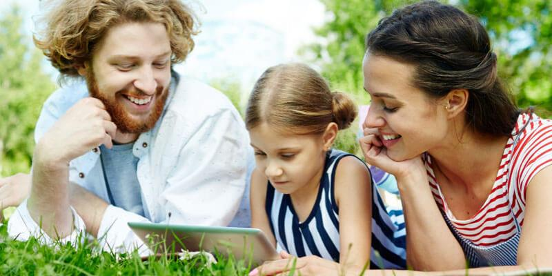A family lying on the grass reading in their back yard. Delta Pest Services provides mosquito control for this family and their home.
